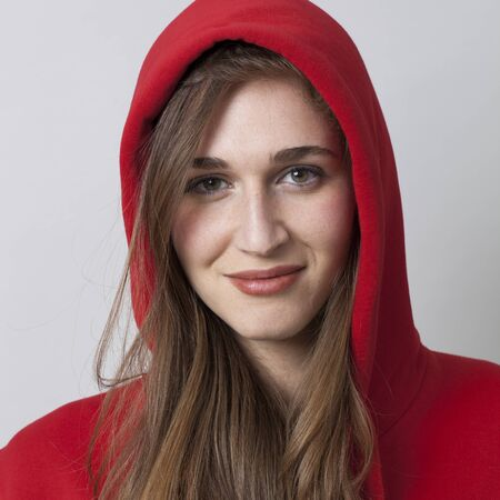 20s: closeup portrait of beautiful smiling 20s woman wearing red hoodie with long hair for cool attitude Stock Photo