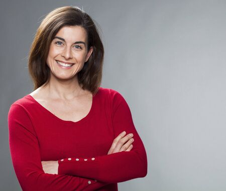 30s: smiling 30s woman with arms folded, wearing colorful sweater, expressing wellbeing and happiness