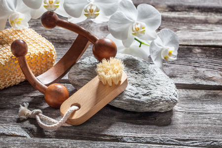indulging: spa beauty treatment concept - symbols of massage, washing-up and nail care for indulging yourself set on old wood, gray texture stone and white orchid flower background for genuine body care decor Stock Photo