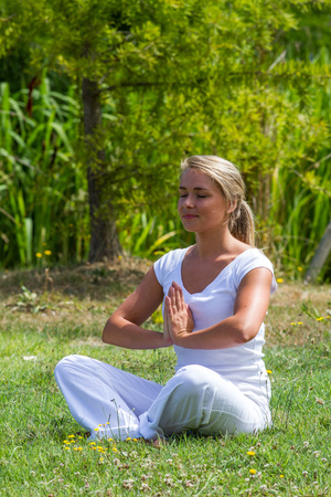 inner peace: outdoors meditation - smiling young yoga woman exercising in lotus praying pose,closing eyes to focus on inner peace to relax and meditate on grass with green bushy background
