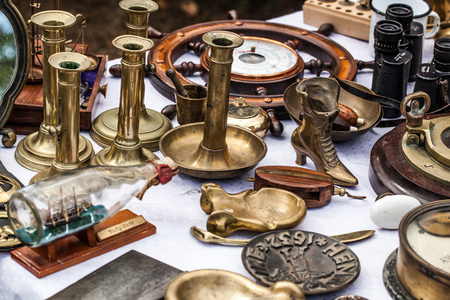 oldie: display of old brass candleholders,ashtrays,miniature boats on glass bottle and other brass objects for collection sold at flea market for antique collection Stock Photo