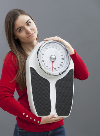 dubious: dubious young woman holding a weighting scale