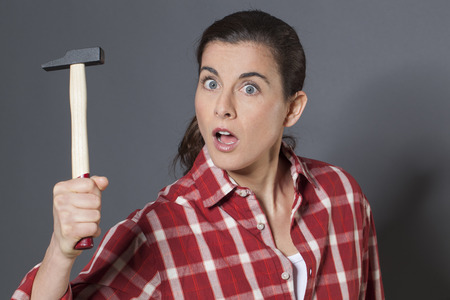 manual work: female DIY concept - surprised brunette woman holding hammer with strength,questioning manual work and home improvement