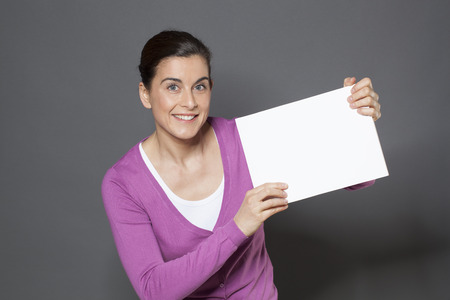 self assurance: thrilled young woman holding a white communication board with good news on Stock Photo