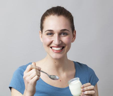 yogur: sonriente mujer joven que disfruta de comer un yogur reci�n hecho en casa del tarro Foto de archivo