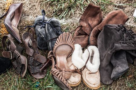 thrift store: mix of second hand leather women shoes and boots on sale at garage sale on grass for welfare, recycling or selling for cheap to cope with over-consumption and fashion Stock Photo