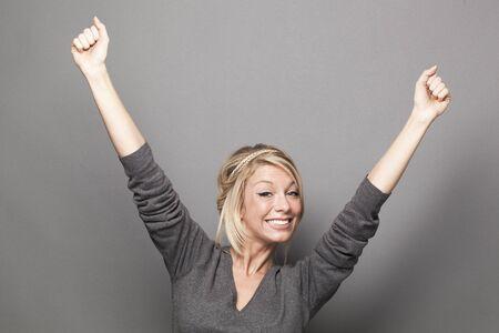 el concepto de éxito - joven rubia éxtasis de ganar un concurso con el lenguaje corporal de la diversión