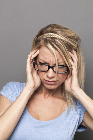 dizzy: ear or headache suffering concept - beautiful young blond woman with eyeglasses having migraine,feeling dizzy or stressed by noise and tinnitus