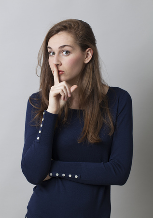 taboo: secret and taboo concept - mysterious 20s girl with long hair wearing navy blue sweater asking for silence with finger on lips,studio shot