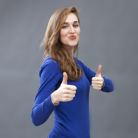 pouting: success concept - lovely young woman wearing a blue sweater showing two thumbs up and a pouting smile for victory
