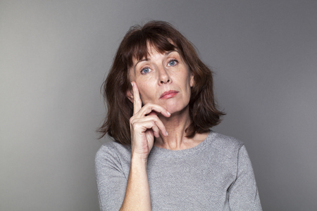 senior pain: unhappy mature woman with brown hair and grey sweater thinking,looking annoyed and concerned