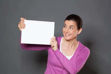 self assurance: excited young woman raising a blank communication board with exciting news on
