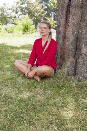 suntanned: wellbeing & tree concept - happy young suntanned blond woman sitting under a tree enjoying free time,natural summer daylight