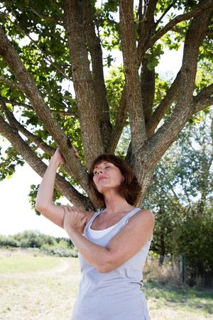 albero della vita: anziano verde wellness - meditando donna matura in possesso di rami degli alberi chiudendo gli occhi in armonia con la natura trovando energia ed equilibrio in un ambiente verde, la luce del giorno d'estate