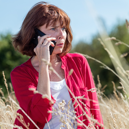 scowl: outdoors communications - concerned senior woman talking on the phone alone in high dry grass field to be quiet,blue sky,natural summer daylight