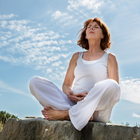 inner beauty: senior zen - breathing 50s woman sitting on a stone in yoga position, closing eyes for serenity and balance in a park,summer daylight,blue sky,low angle view