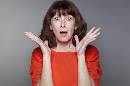 desilusion: sorpresa y decepción concepto - hermosos 50s mujer que llevaba un suéter rojo que expresa sorpresa con ambas manos y en la cara Foto de archivo