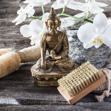 exfoliation: spa beauty treatment concept - symbol of cleansing and exfoliation for inner beauty with Buddha on old wood, gray texture stones and white orchid flower background for authentic zen decor Stock Photo