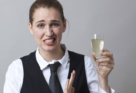 bubbly: Unhappy young woman wearing uniform of wine waitress refusing glass of white bubbly wine