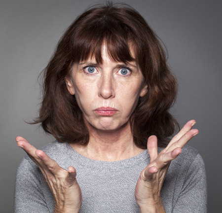 Primer plano retrato de mujer frustrada de 50 perdiendo la fe, haciendo un mohín con palma manos abrió la renuncia Foto de archivo