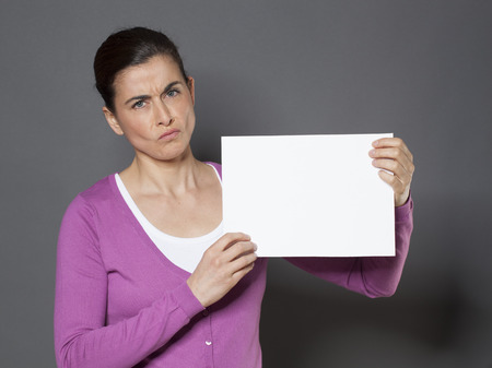 criticize: unhappy 30s woman displaying her disappointment on a banner