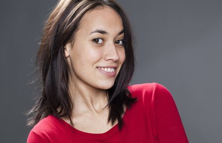 seduction: closeup on sexy multiethnic 20s girl wearing red sweater expressing happiness and seduction Stock Photo
