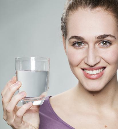 lachende jonge mooie vrouw, gekleed in paars shirt tonen van glas zuiver water uit de kraan Stockfoto