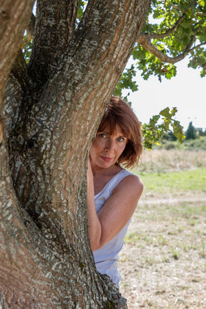 inner peace: senior green wellness - shy mature woman hiding behind a tree in harmony with nature seeking for serenity and inner peace outdoors,summer daylight