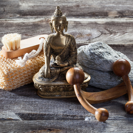 inner beauty: spa beauty treatment concept - inner beauty with washing-up, exfoliation and massage accessories with spiritual symbol such as Buddha on old wood and gray stones background for authentic zen decor Stock Photo