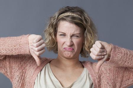 desilusion: concepto decepción - disgustado mujer joven con el pelo rubio rizado haciendo doble pulgares hacia abajo para el desacuerdo y náuseas