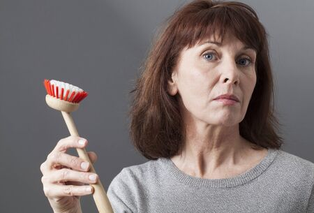 arrogancia: hermosa mujer madura que muestra cepillo de plato para lavar los platos pregunta sobre papel