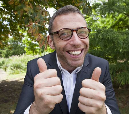 weirdo: mad scientist outdoor concept - thrilled businessman smiling with double thumbs up in green background for corporate management,natural summer daylight Stock Photo
