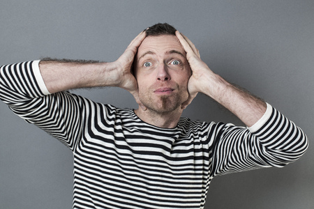 eyes wide: surprise and success concept - handsome middle age man acting surprised with both hands on head with casual goatee and eyes wide opened