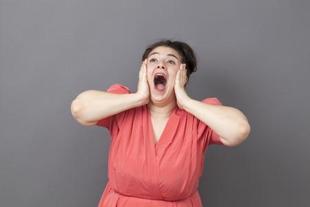 donne obese: sorpresa e il concetto di successo - estroversa grande donna che urla per la sorpresa e la felicità con l'annata abito rosa