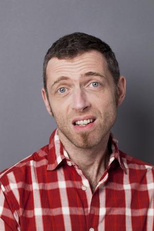 decepci�n: concepto decepci�n - decepcionado hombre de mediana edad con el pelo corto molestar al expresar remordimiento o renuncia Foto de archivo