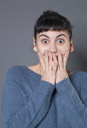 shyness: surprise and success concept - playful 20s woman wearing a blue winter sweater hiding her smile behind both hands for surprise and shyness