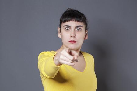 firmeza: mujer joven morena aturdido mirando a alguien con el dedo �ndice hacia adelante reconociendo y acusando a alguien con miedo en los ojos