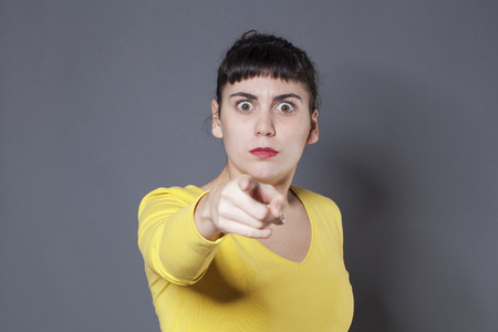 recognizing: stunned young brunette woman staring at someone with index finger forward recognizing and accusing someone with fear in eyes Stock Photo