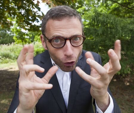 mad scientist outdoor concept - crazy businessman showing his mad face and strange hands in foreground in green environment for corporate involvement,natural summer daylight