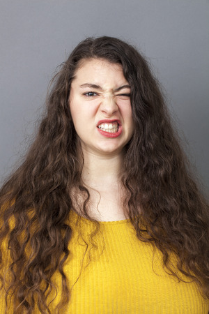 stressed out: stressed out overweight 20s woman with long brown hair showing teeth for expressing stress and bad temper Stock Photo