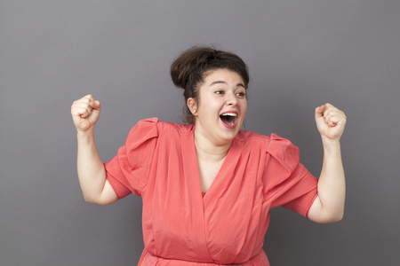 extrovert: success concept - extrovert young big girl wearing a vintage dress with fists up expressing her achievement and happiness Stock Photo