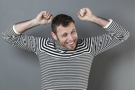 regret: success concept - excited young man wearing a casual striped sweater raising both hands and fists for disappointment and regret