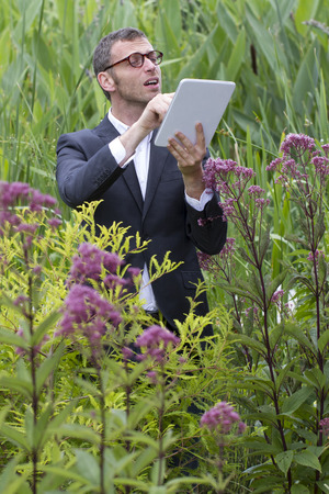 botanist: tablet usage outdoors - fun mad scientist or botanist working with wireless tablet standing alone in middle of jungle of long exotic green grass and flowers,natural summer daylight Stock Photo