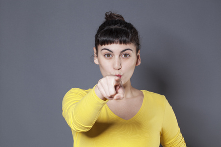 reproach: smiling young woman staring at someone with finger pointing forward with blaming attitude and self-assertion Stock Photo