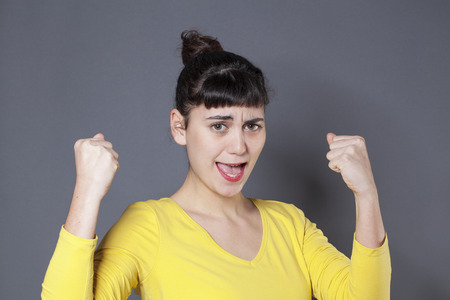 regret: success concept - disappointed young woman wearing a yellow sweater expressing her regret with hands and fists up Stock Photo