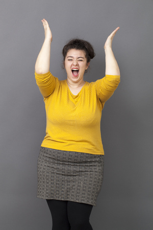 extrovert: success concept - extrovert young overweight girl wearing a yellow sweater expressing her achievement and joy in clapping hands up Stock Photo