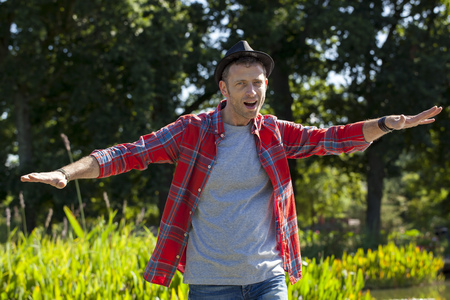checked shirt: male fun outdoors - free middle age man with a hat and casual checked shirt opened playing like a plane in park for happiness and escape from the city,natural green background