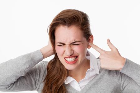 耳鳴りコンセプト - 痛みを伴う頭痛を有するカバー閉じた耳、物語の彼らの側面を聞きたくない騒音に悩まされ激怒の若い女性