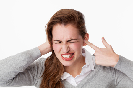 tinnitus concept - enraged young woman having painful headache,covering closed ears,annoyed by loud noise not wanting to hear their side of story