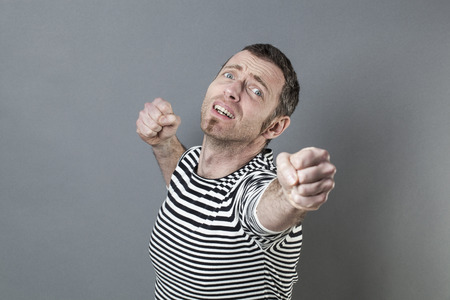 onwards: desperate 40s man willing to achieve something with determination and passion with fists onwards and backwards with a theatrical expression Stock Photo